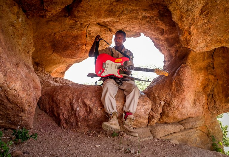 Security escort takes a break from the heat to play guitar in Somaliand